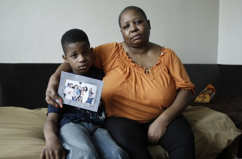 Angela Jenkins, holds a family photo as she sits with her grandson, Lavelle Martin the day after her son Larry was stabbed to death. Susan Du / Homicide Watch