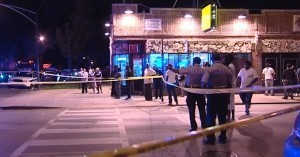 Police and a crowd gather near a scene of a shooting in the 7500 block of South Stewart Tuesday night. | Network Video Productions