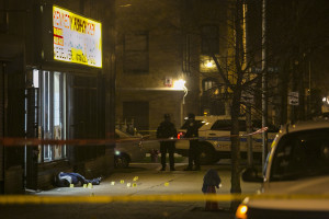 Chicago Police investigate in the 2400 block of East 72nd Street in South Shore, where a man was shot to death early Wednesday. | Ashlee Rezin/Sun-Times
