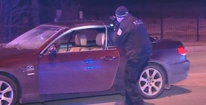 An investigator photographs the inside of a car that a 22-year-old man was fatally shot in early Friday on the Northwest Side. | Network Video Productions