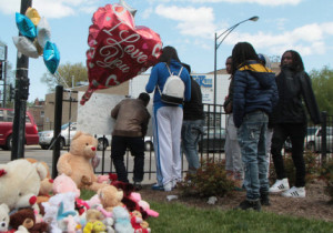 A memorial of balloons and stuffed animals lay on the ground in front of the Parkway Gardens complex for 15 year old DeKayla Dansberry who was killed Saturday night.  Corey Brooks, of New Beginnings Church, had a vigil for the 15 year old at his church. | Leslie Adkins/For the Sun-Times