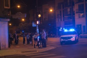 People stand on the corner of Chicago and California avenues after a shooting nearby early Saturday morning. | Matthew Hendrickson/Chicago Sun-Times