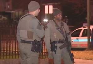 Officers armed with rifles guard the South Chicago block where multiple people were shot at a party early Saturday. | Network Video Productions