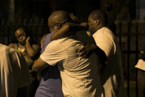 Two people hug outside in the 1400 block of North Leclaire in Austin, where a son found his parents stabbed to death inside their home early Sunday. | Ashlee Rezin/Sun-Times