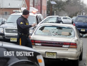 A shattered rear window is seen on a vehicle parked on East State Street in Trenton as police investigate a shooting Tuesday Feb. 26, 2013. (Trentonian photo/Jackie Schear)