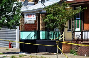A black cloth barrier is seen in front of an East State Street home on Sunday morning following an overnight wave of violence in the city that left three dead. Police were seen collecting evidence at the location on Sunday Aug. 4, 2013. (Trentonian photo/SCOTT KETTERER)