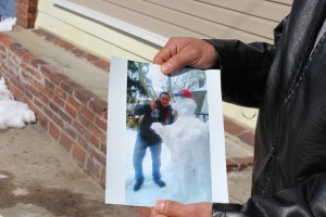 A friend shows the photo of Julio Cesar Cruz. Cruz, a resident of Trenton's South Ward was beat to death Saturday evening in front of his home. Trentonian Photo/CARLOS AVILA.