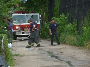 Firefighters clean the scene of a murder that occurred in an alley in the 400 block of Cuyler Avenue - July, 25, 2014. (Trentonian photo/Penny Ray).