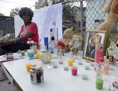 A woman who did not wish to be identified sits at a memorial for Iyeesha Kia Thomas Tuesday Oct. 28, 2014 on Brunswick Avenue in Trenton. The woman said the memorial will remain through Sunday. (JACKIE SCHEAR—THE TRENTONIAN)