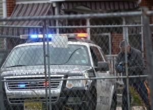 Trenton Police examine a vehicle on WIlson St. that was shot at and struck by a burglary suspect. Police returned fire and the suspect died at Capital Health Regional Medical Center.  John Berry - The Trentonian.