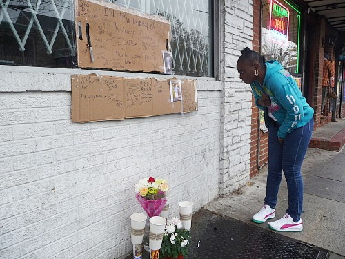 A passerby stops to view a makeshift memorial in honor of Rodney Burke on Hamilton Avenue. Nov. 6, 2014 - Penny Ray