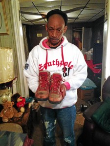 Milton Covington holds his brother John's boots that he retrieved from the crash scene where his brother was killed. (David Foster - The Trentonian)