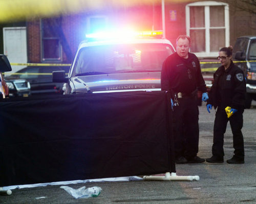 Trenton police investigate a murder in the 100 block of Hudson Street Wednesday afternoon. The victim is on the ground  behind the black curtain. (Gregg Slaboda - Trentonian)