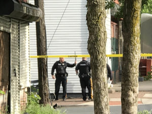 Police guard the body of a homicide victim as the suspect is barricaded inside of a home on the 300 block of Centre St. in Trenton. (Penny Ray — The Trentonian)