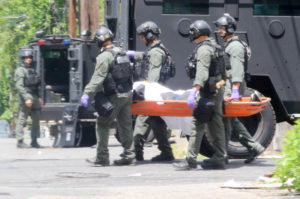New Jersey State Police TEAMS unit officers are seen moving the body of a man killed during a shootout with police. The alleged shooter barricaded himself inside after a shootout with police on May 10, 2017. (Penny Ray - Trentonian)