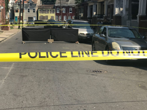 A murder victim lies in the street on Sanford St in Trenton Friday as police process the scene. John Berry - The Trentonian