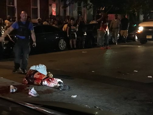 "A man who was shot and arrested by police lays outside the Roebling Wire Works. The man was identified by sources as ""Dada"" or Davone White. White was charged as one of the suspected shooters in the mass shooting at Art All Night on June 17, 2018. (Photo courtesy of Planet Princeton.)"